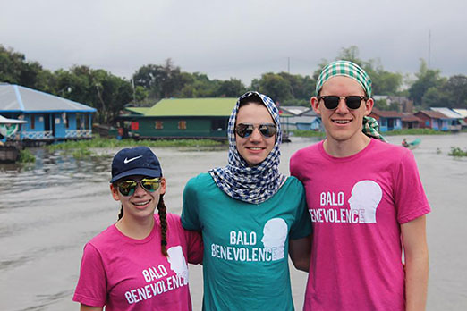 Senior Mimi Ricanati, sophomore Kevin LaMonica and senior Gus Mahoney wear Bald Benevolence T-shirts on a recent service trip to Cambodia.