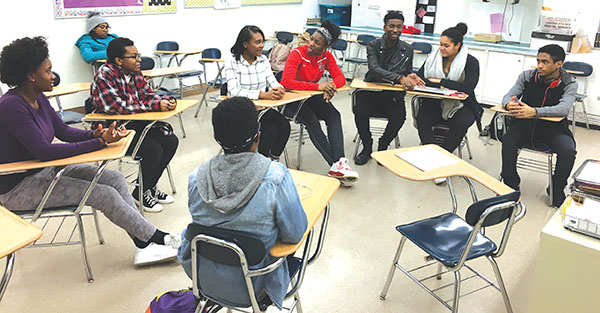 """Members of the high school's chapter of the NAACP engage in discussion in Room 157. """"Through the [NAACP's] Race and Culture Committee, we'll be doing different discussions and different activities, maybe even field trips, based around bringing racial and cultural awareness,"""" said Siraj Lee, senior and NAACP leader."""