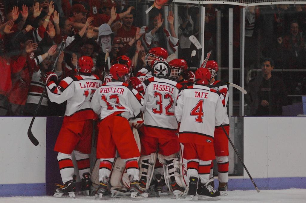 The+team+cheers+against+the+glass+with+fans+after+sophmore+Peter+Shick+scored+the+game+winning+goal+in+overtime.+The+team+went+on+to+beat+Brecksville+High+School+on+Nov.+24%3B+their+record+is+now+2-0.%0A