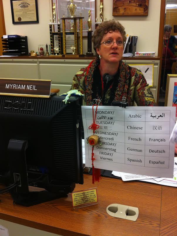 Administrative Assistant Myriam Neils desk in the main office displays the schedule for the high schools language table. All students are welcome. The only requirement is that the designated language is spoken throughout the lunch period.