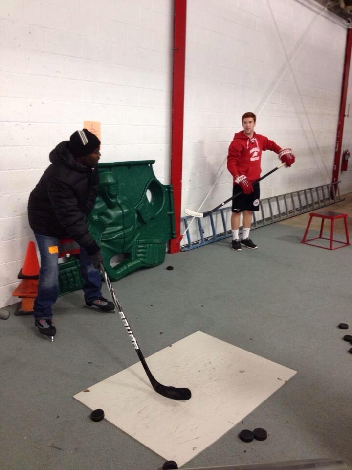 Hutchings+shoots+some+pucks+with+junior+hockey+player+Nathan+Christman.