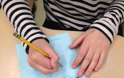 In a preview of college exam practices, students write essay responses in Blue Books.