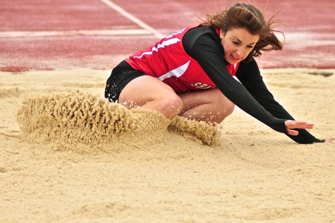 Junior Hannah Heverling lands into the sand after a long jump attempt April 30, 2014.