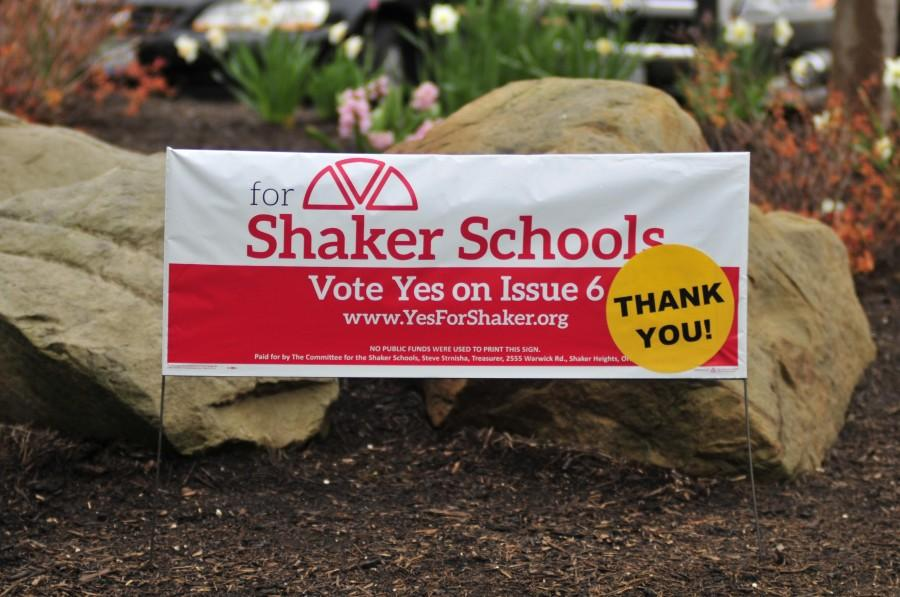 Volunteers placed stickers on pro-levy signs thanking the community for its approval this morning.
