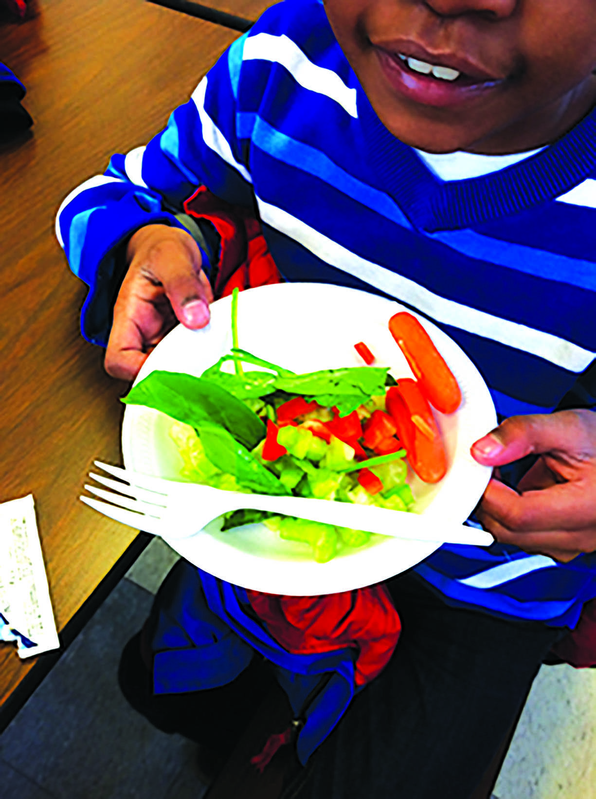 An excited student poses with his bowl of vegetables from the 'Offering Bar' ar Onaway. An Offering Bar bowl is only $1, and is planned to move to the high school and the other elementary schools in the future, according to AVI Director Amanda Schindley.