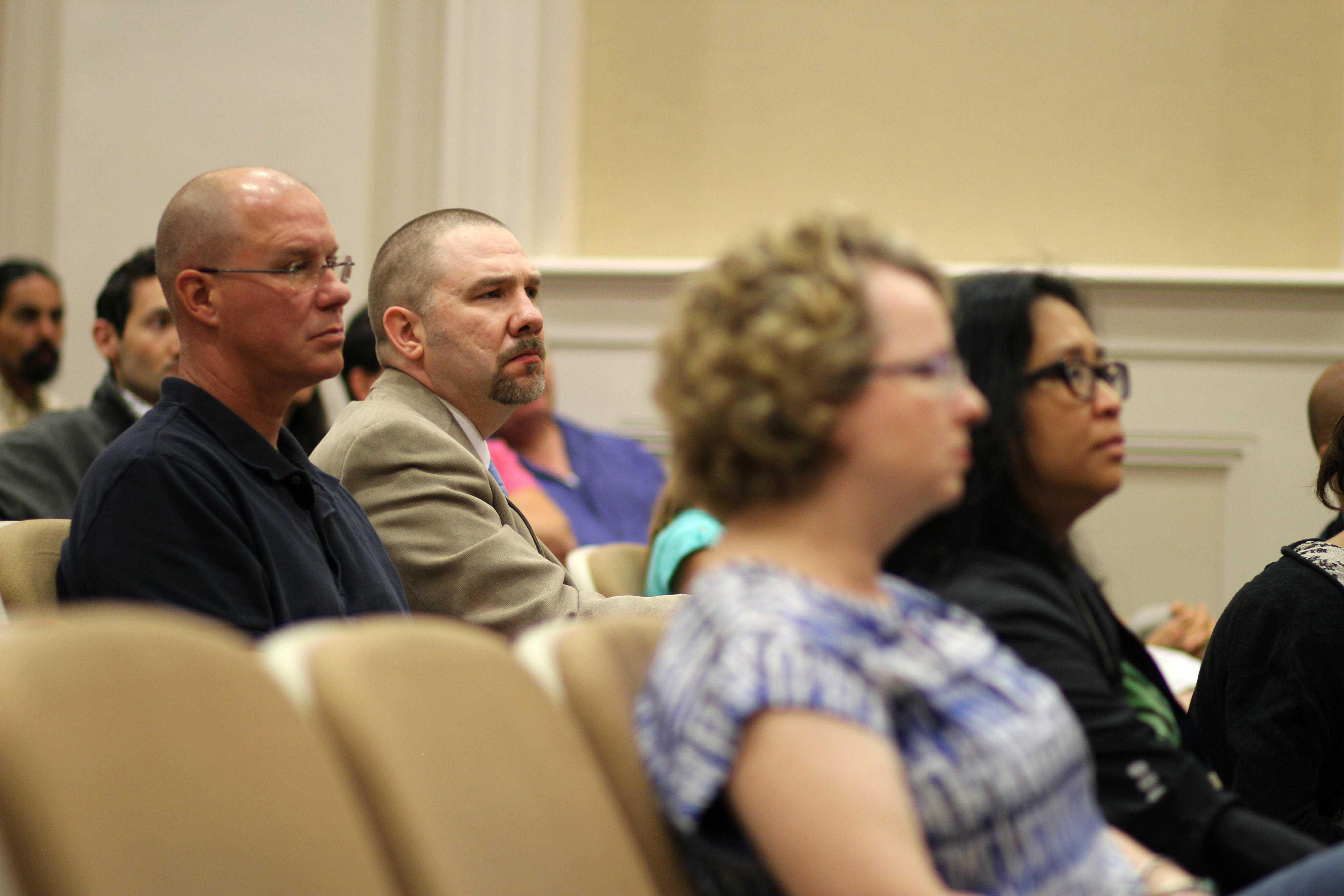 Social studies teachers Sarah Davis and Tod Torrance and SHTA President John Morris listen as Sen. Sherrod Brown addresses the spike in standardized testing.