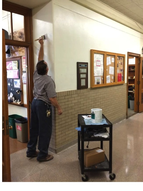 Custodian painting over stenciled room numbers Sept. 1, 2015.