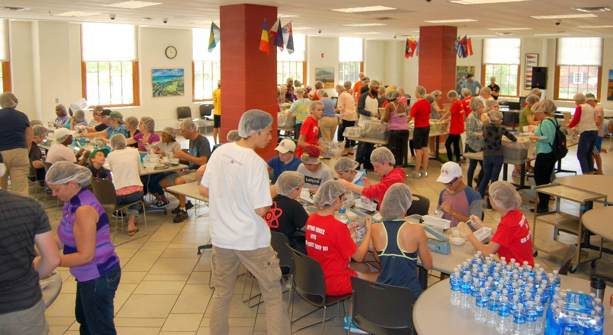 Volunteers packing the meals for Stop Hunger Now in the high school's lower cafeteria.