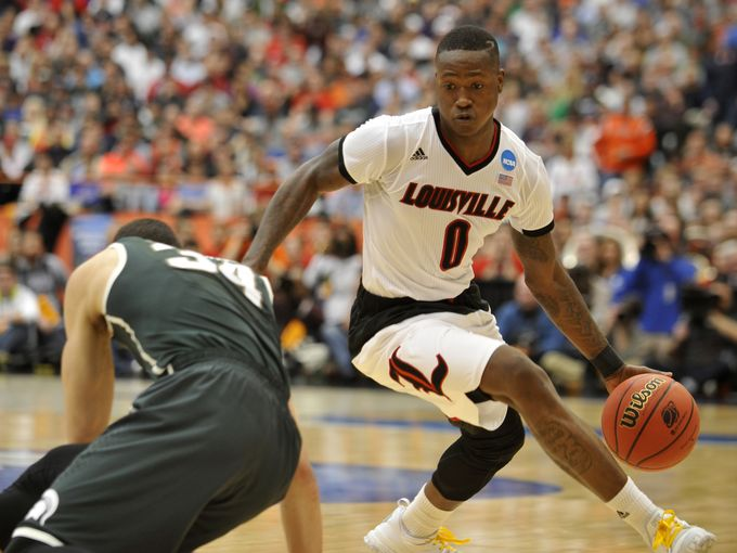 Louisville guard Terry Rozier ('12) dribbles past Michigan State's Matt Costello during the Cardinals' Elite 8 loss March 29, 2015.