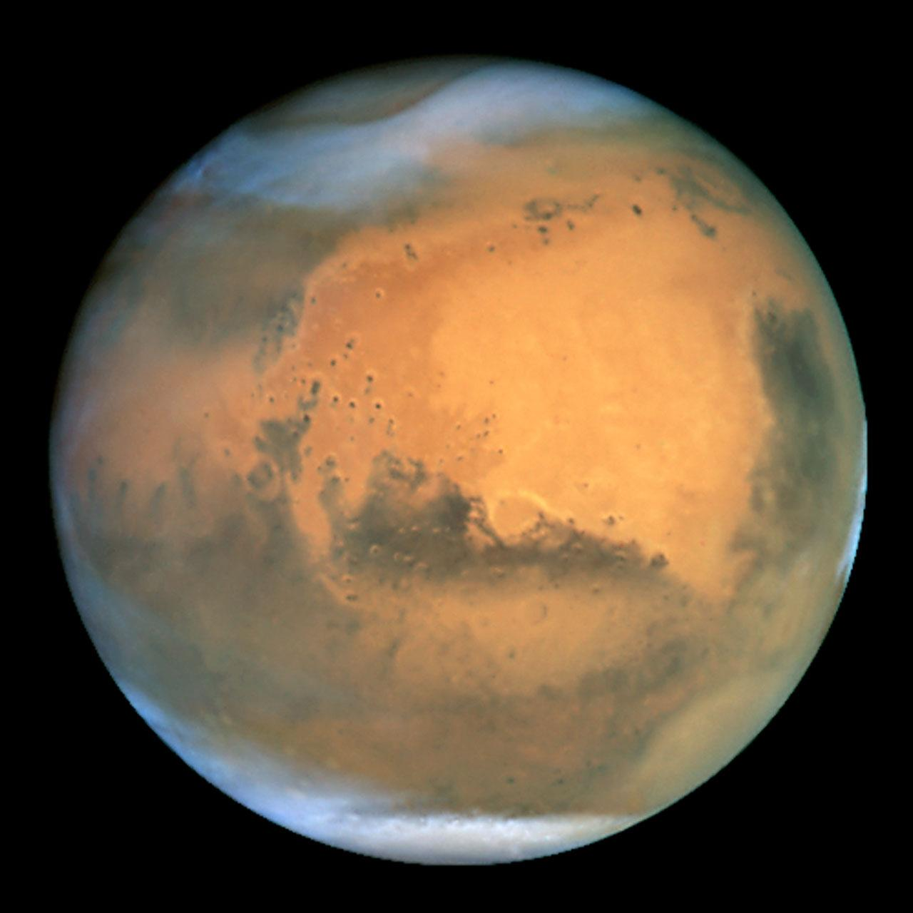 Frosty white water ice clouds and swirling orange dust storms above a vivid rusty landscape reveal Mars as a dynamic planet in this sharpest view ever obtained by an Earth-based telescope. Scientisits have found water on the dusty planet, suggesting possible life. Acknowledgements: J. Bell (Cornell U.), P. James (U. Toledo), M. Wolff (Space Science Institute), A. Lubenow (STScI), J. Neubert (MIT/Cornell)