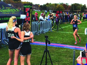 Junior Mimi Reimers and sophomore Sophie Carrier watch teammate sophomore Alexa Jankowsky cross the finish.
