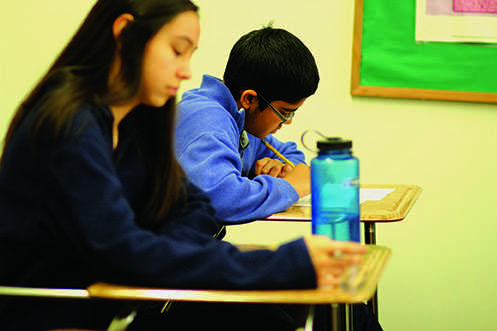 Sophomore Advanced Placement United States History students Caitlin Culina and Gautam Apte take a quiz Dec. 8. Students who take classes such as these can confront several tests or quizzes on the same day despite the high school's testing schedule policy.