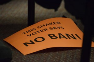 A sign sits at the feet of a community member. The neon orange, pink, yellow and green signs were handed out by Clint Evans before the meeting.