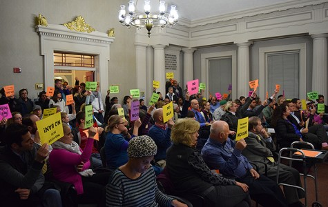 Audience members hold neon orange, yellow, pink and green signs while Mayor Earl Leiken speaks.