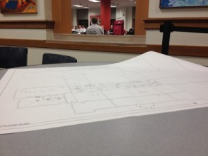 A blueprint of the high school lies unfurled on a cafeteria table