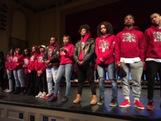 Sankofa cast members stand on the edge of the stage of the Large Auditorium as Mekkah Hussameden speaks about Trayvon Martin at Sankofa 2016.
