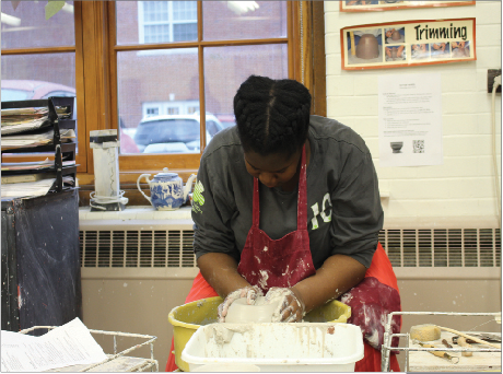 """Sophomore Dawn Falokun shapes a clay piece on a pottery wheel. Art students at Shaker enjoy the break from daily stressors that art gives them. """"For me it's like a way to step back from the school and academic part and just focus on my other hobbies,"""" said senior Lily Schulte-Lawrence."""