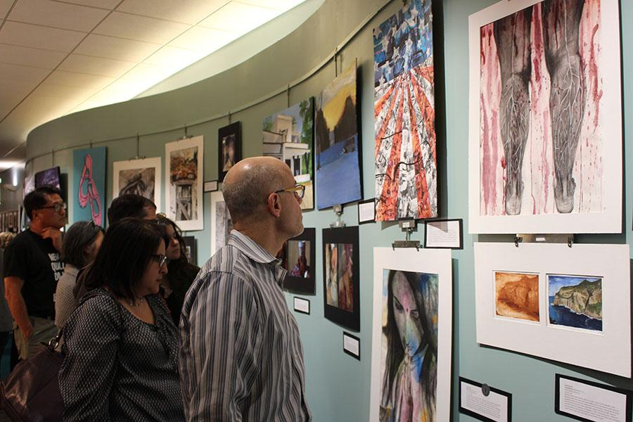 Attendees view student artwork at the annual Art Exposed art show on the second floor of the Shaker Heights Public Library on Lee Road May 6.