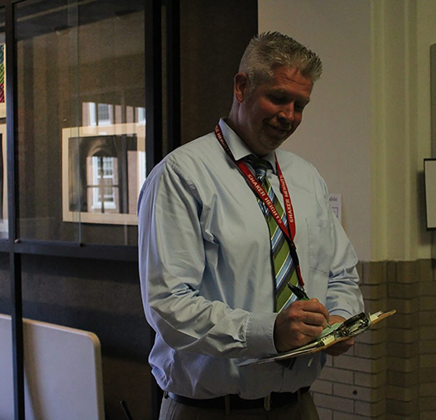 Dean of Students Greg Zannelli writes a tardy pass for a late student. Tardiness is a tier-one discipline offence punishable by detention or Saturday school. Tier one discipline also includes dress code and cell phone violations.