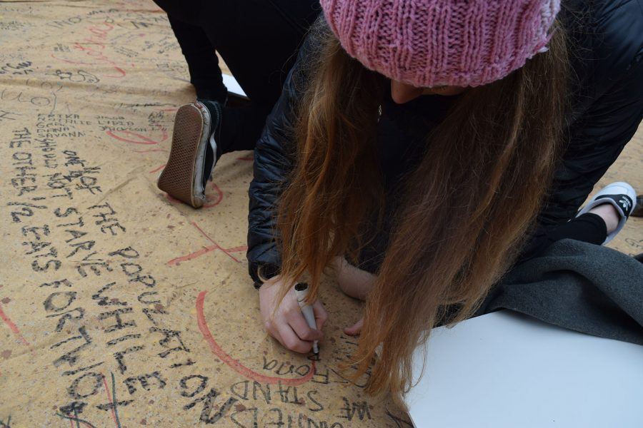 Rioters sign a poster in solidarity for women's rights.