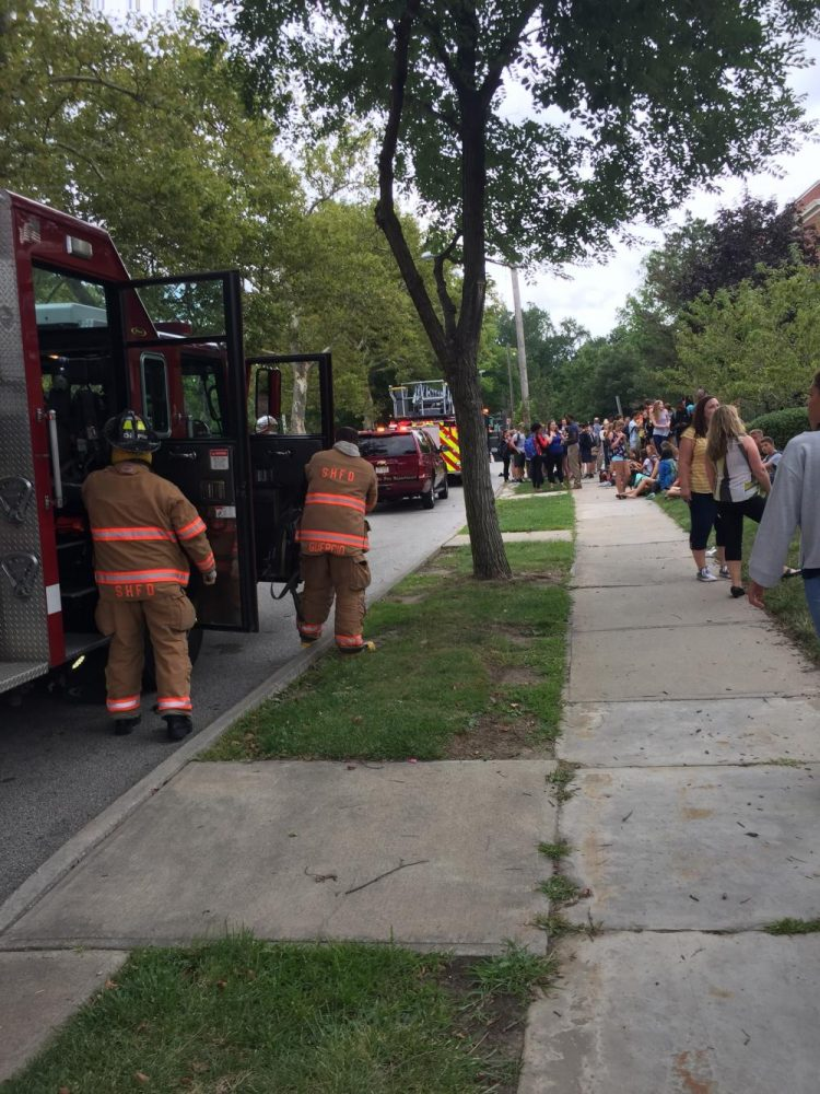 Students gather on the sidewalk next to firetrucks and fire department vans.