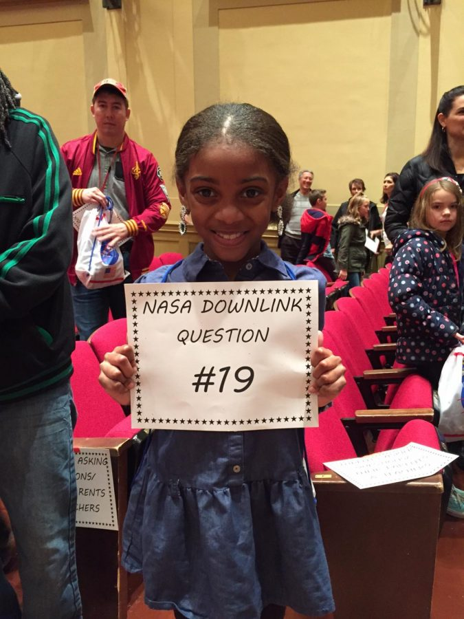 An elementary school student stands with the sign for her question after the assembly.