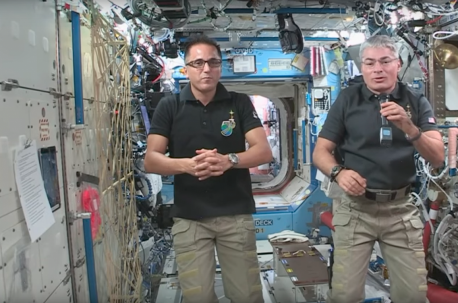 Joe Acaba, left, and Mark Vande Hei, right, float as they speak to students about their time in the International Space Station.
