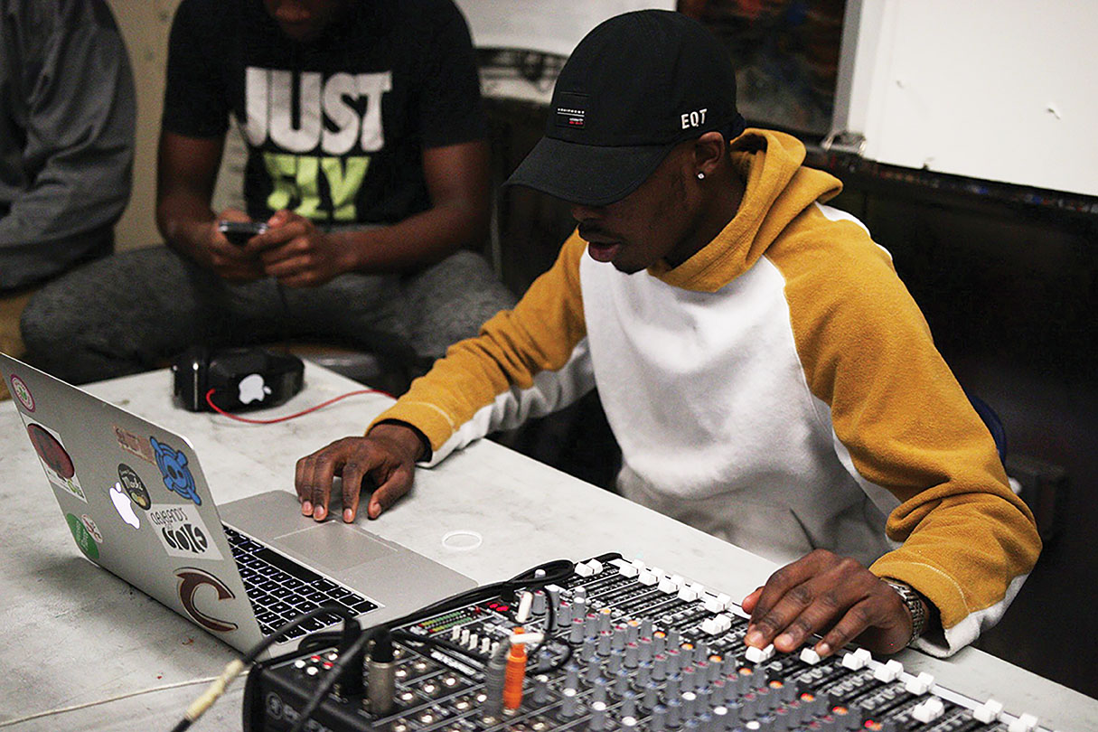 Producer Lawrence Butler ('13), teaches Sankofa performers how to work a soundboard.
