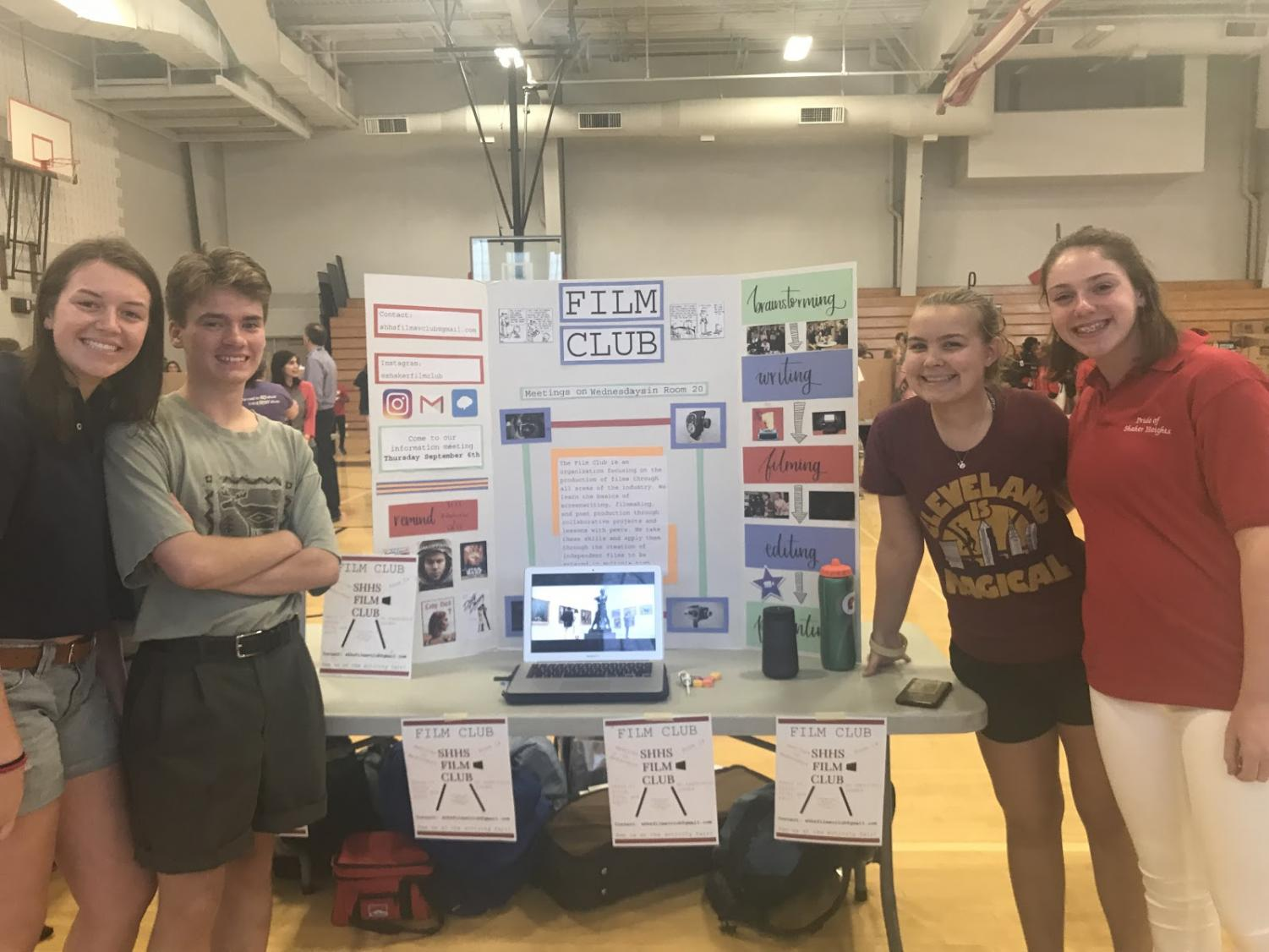 Executive Film Club team members Emie Coffman, Clovis Westlund, Rebecca Rhodes and Zoe Rosenfelt stand by their table at the activity fair.