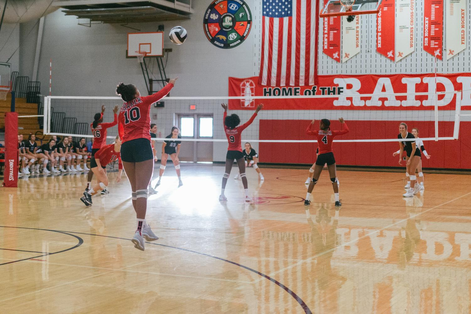 Freshman India Williams serves a ball, while the rest of the team is ready for the play to begin. Varsity volleyball team faces  Brunswick on Oct. 4.