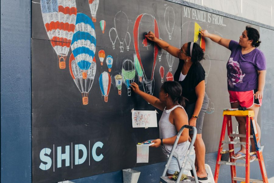 Honors drawing student Alona Miller, assisted by a teacher and student, draws her first place design on the chalk wall in the Van Aken District.