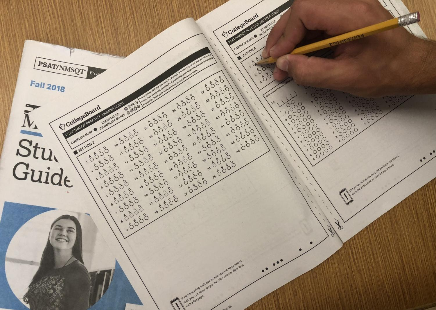 Student takes a practice exam in his PSAT practice booklet. Ohio law requires that schools administer ACT or SAT to all grade 11 students and pays for the administration but does not require or support the PSAT.