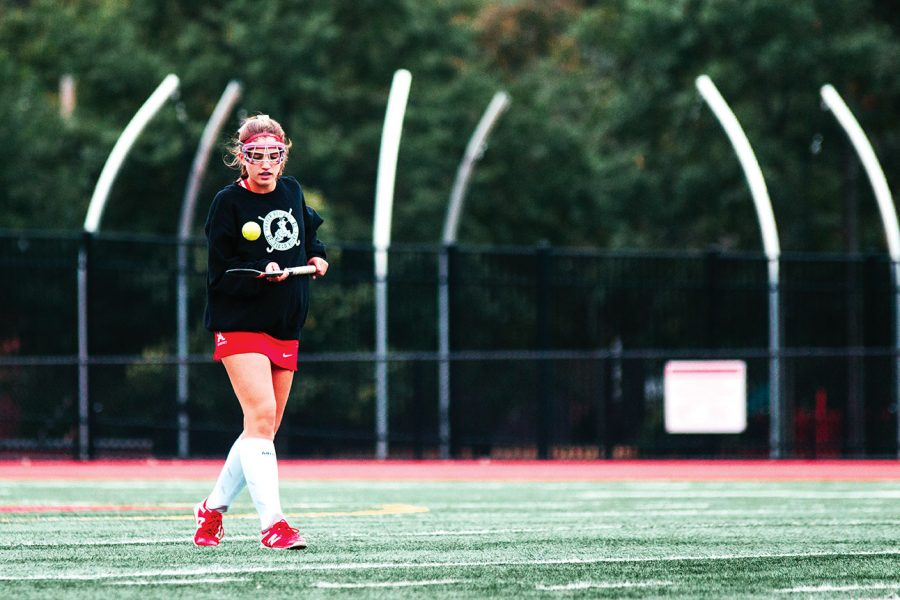 Junior Reese Pulver hits a field hockey ball into the air as she warms up for a home game.
