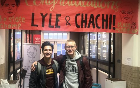 Senior Lyle Yost, who won his third consecutive state diving competition, and senior Charlie Gustafson, state runner-up in the 100-meter butterfly, smile in front of a congratulatory poster.