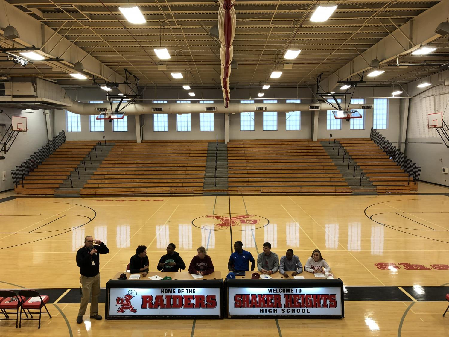 The seven athletes sit in front of a crowd of friends, coaches and family as they sign their letters of intent.