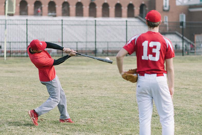 A baseball coach demonstrates the proper technique of hitting a baseball.