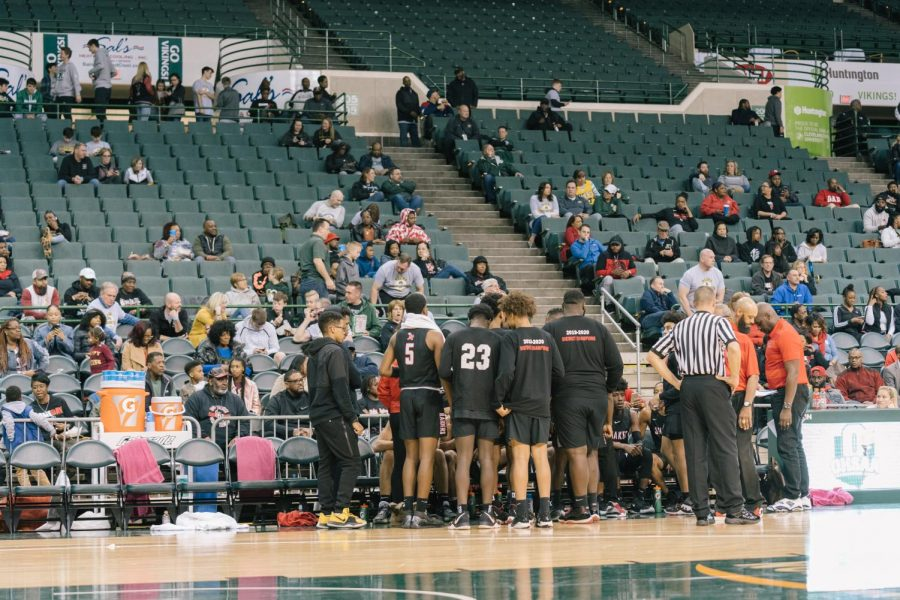 The varsity basketball team huddles during a timeout in the regional semifinal against Canton McKinley March 11 at Cleveland State University. Only four family members per player were permitted in the arena.