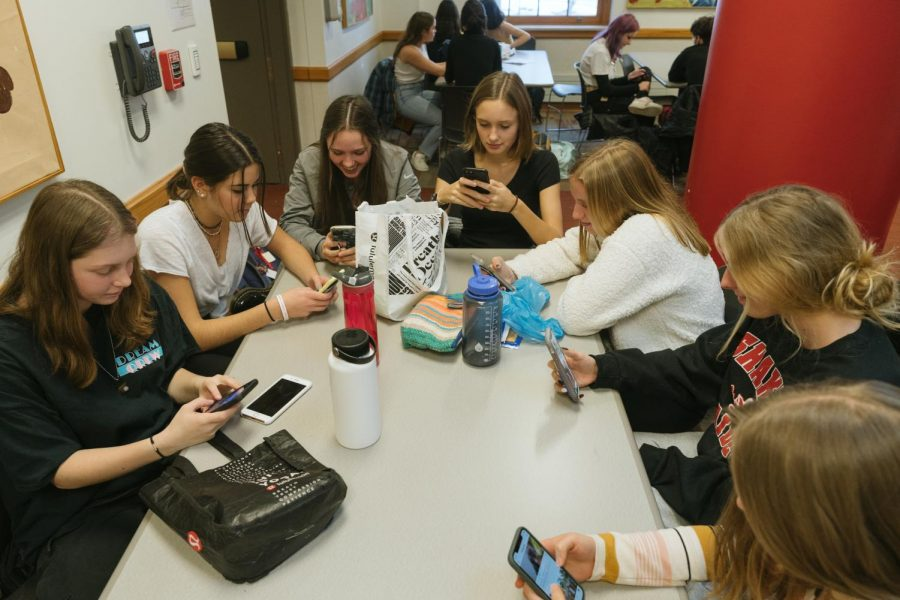 Students around the lunch table use their phones instead of interacting with one another.