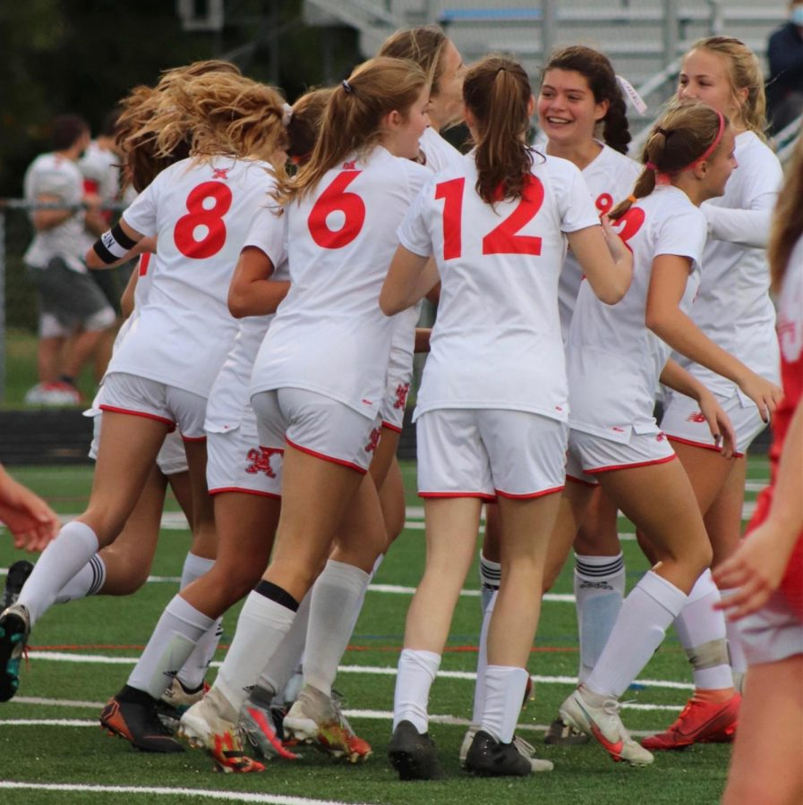 The+varsity+woman%27s+soccer+team+celebrates+after+a+goal+against+Hawken+on+Sept.+29