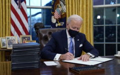 Biden signing documents in the Oval Office.