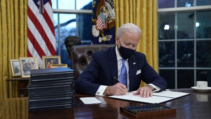 Biden+signing+documents+in+the+Oval+Office.+%0A