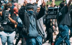 Man holds up peace signs at a May 30 protest in downtown Cleveland.