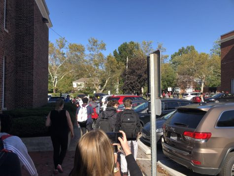 Students and staff exit the building through the North Gym Lobby after the third fire alarm